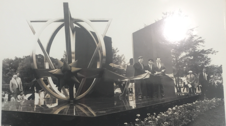 A photo of a photo in Jefferson's display case. The photo is of the ribbon cutting ceremony held at the first unveiling of Thomas Jefferson High School.