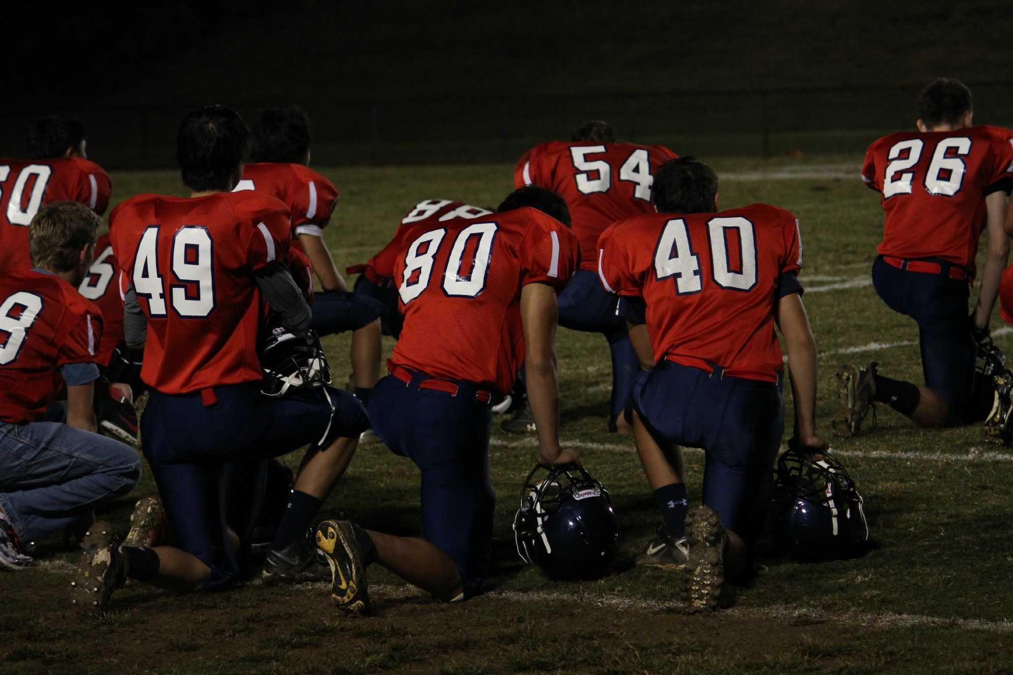 Jefferson players kneel in respect for injured junior Daven Kim.