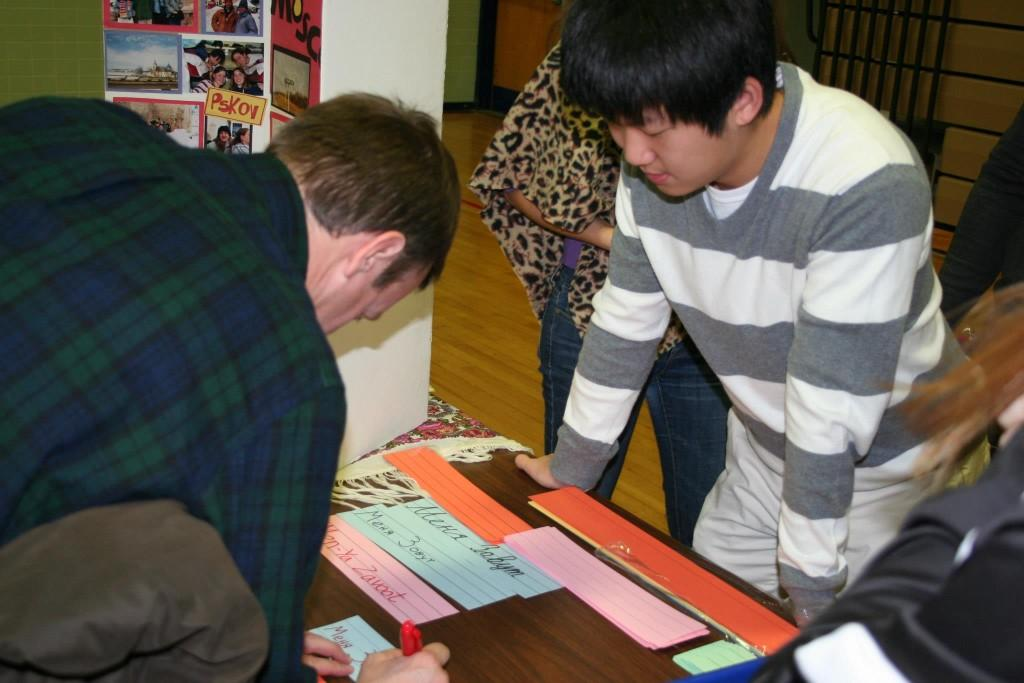 Russian Honor Society member Kyu Kim instructs people how to write their names in Russian as a part of their booth at tjMUN Global.