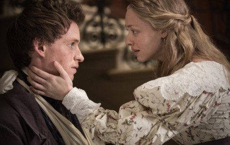 Cosette (Amanda Seyfried) embraces Marius (Eddie Redmayne) after the attack at the barricade in the Les Misérables film.