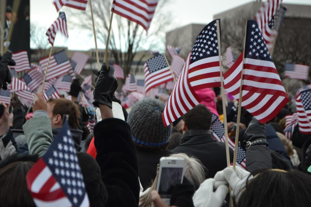 Spectators wave flags while watching the Inauguration.