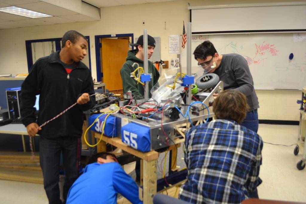 Members of the FIRST Robotics team work on putting the finishing touches on their robot.