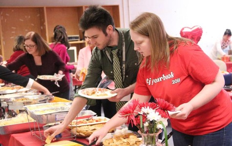 English teacher Erinn Harris and Communications Systems Research lab director Paul Kosek choose from the dishes provided by the PTSA for the Valentine's Day lunch.