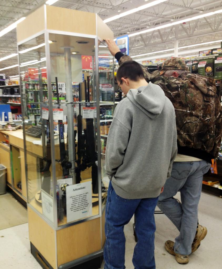A+father+and+son+look+at+the+rifle+case+at+a+Wal-Mart+in+Warrenton.