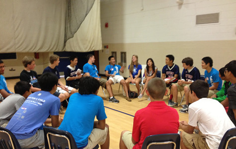 BigSibs and LittleSibs sit in a circle in Gym 2 as they play icebreaker games.