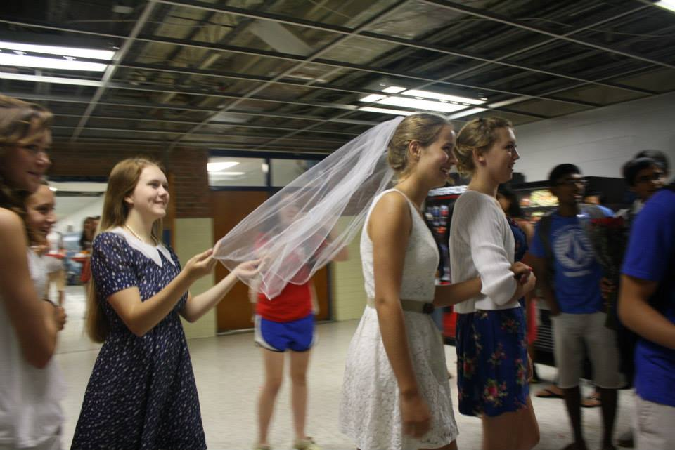 Junior Sophie Bennett is led by juniors Annie Thomas and Caroline Culberson down the aisle.