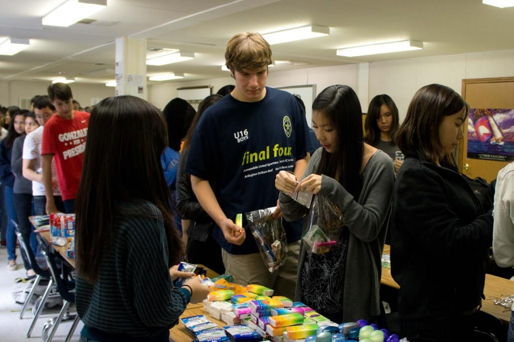 Junior Seth Jaffe and senior Florencia Son fill their care packages with toiletries.