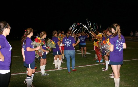 Field hockey players create a tunnel for the seniors to run through.
