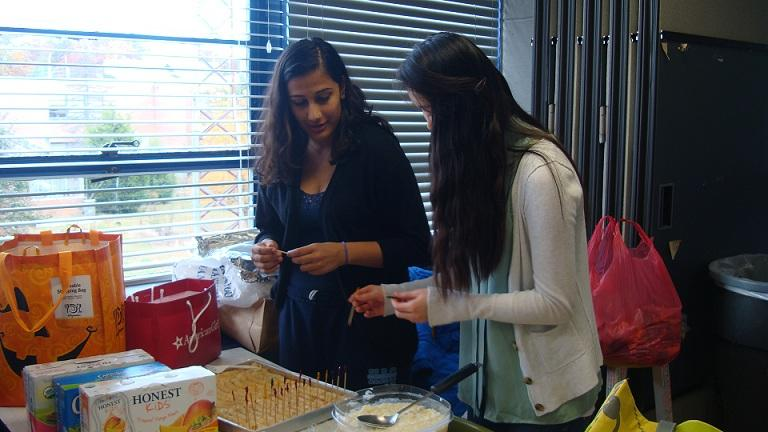 Sophomore Shritika Dahal and junior Melissa Wu prepare for the Hunger Banquet.