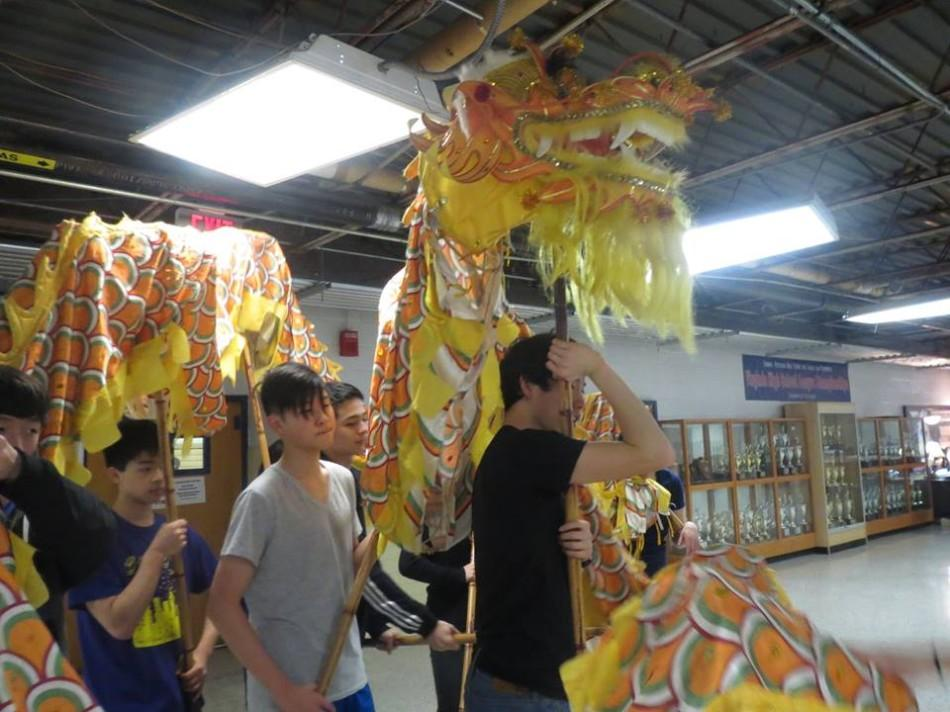 Chinese Honor Society dragon group rehearses using their puppet.
