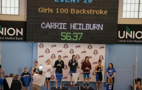 Photo courtesy of www.colonialathletics.org. Junior Carrie Heilbrun stands on the podium after winning 100 backstroke at the state conference.