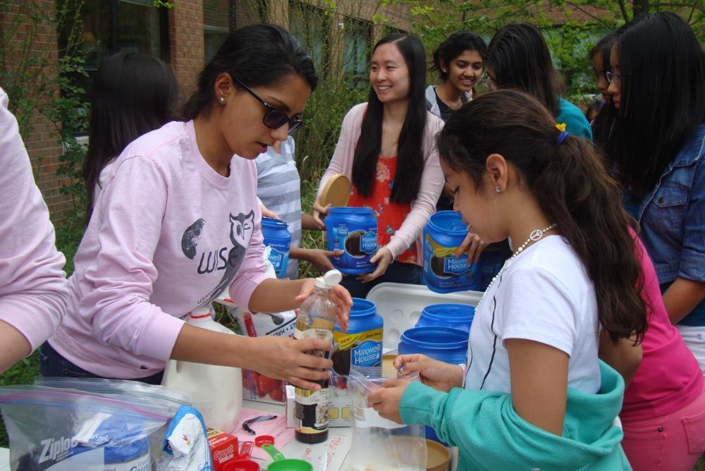Senior Priya Seetharaman helps a Weyanoke student make an ice cream during an eighth period meeting of Women In Science and Engineering (WISE).