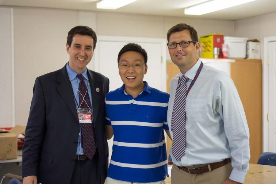 Principal Evan Glazer (left) and Assistant Principal Shawn DeRose (right) surprised rising senior Brandon Kim (center) in his fourth period exam period when they announced that his submission had won the One Question contest.
