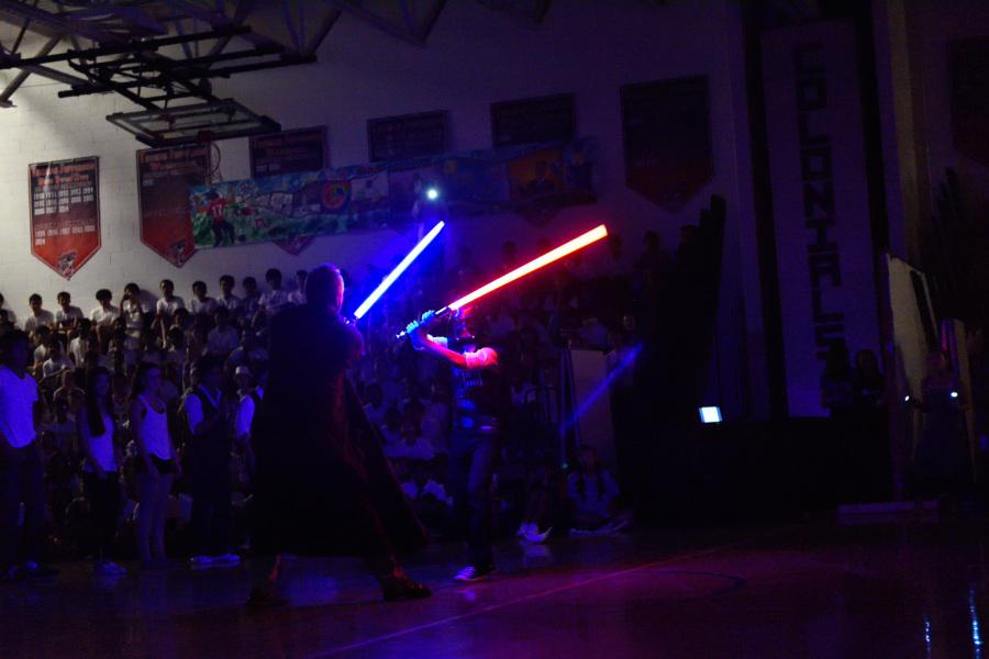 Physics teacher and Class of 2015 sponsor Adam Smith and senior James Jung duel with light sabers during senior MEX.