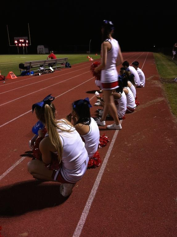 The Colonials cheerleading team takes a water break at half time and waits for the beginning of the third quarter.