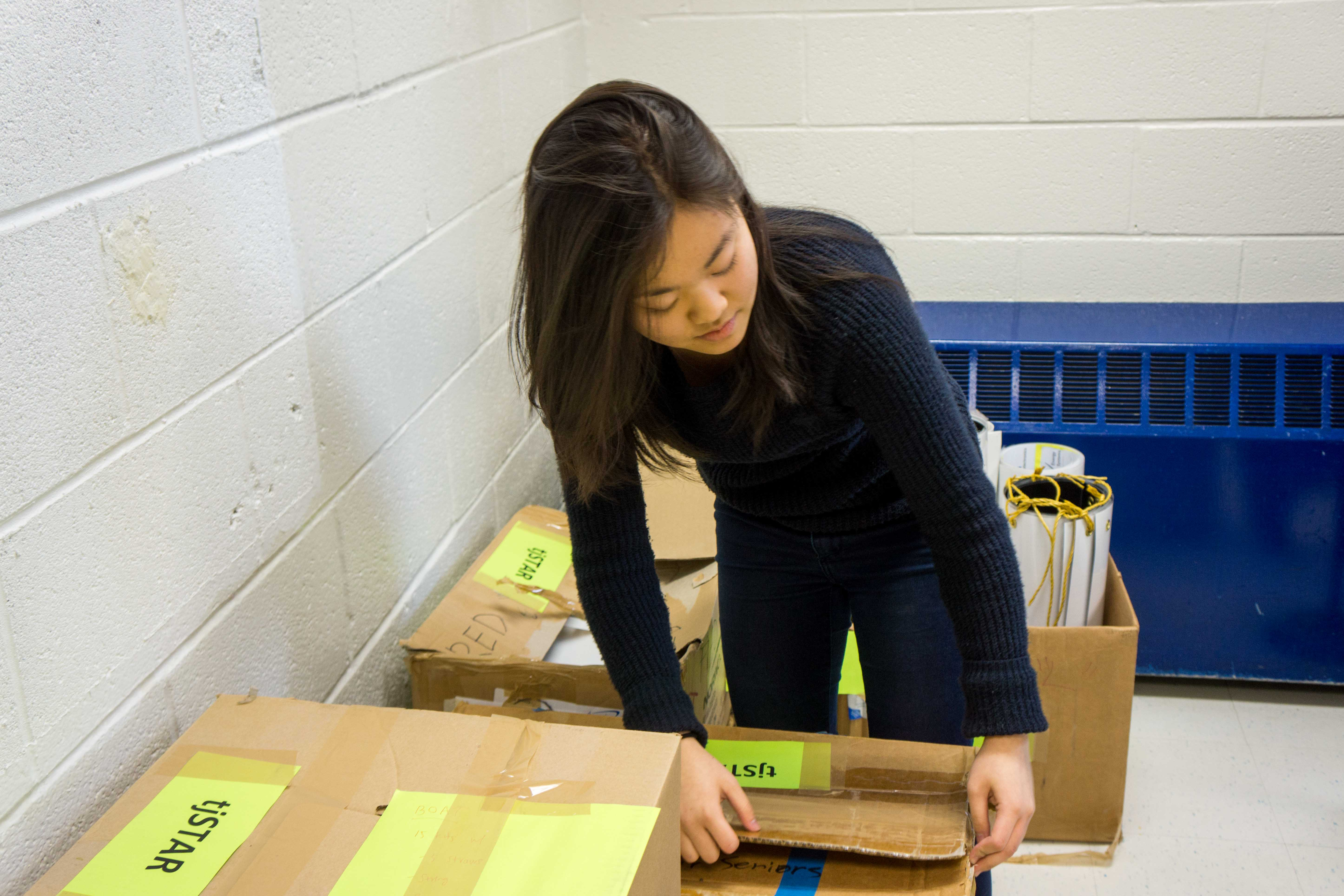Senior Anna Tsutsui, co-chair of the tjSTAR Planning Committee, conducts an inventory of materials from previous years.
