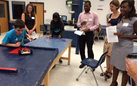 INCOSE representatives and other tour members watch one student test their robot in a maze during the