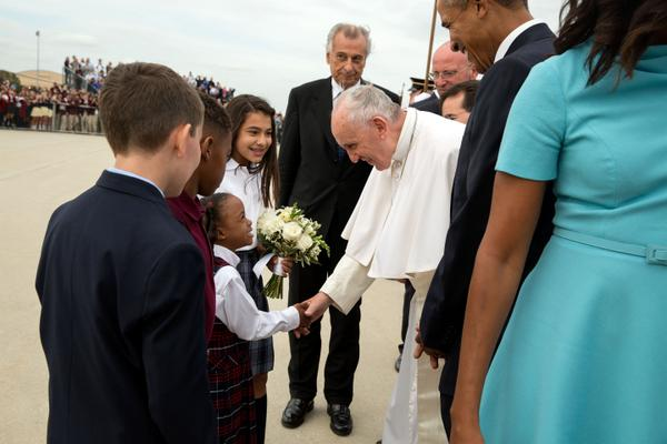 Pope Francis greets children, while President Barack Obama and first lady Michelle Obama look on.