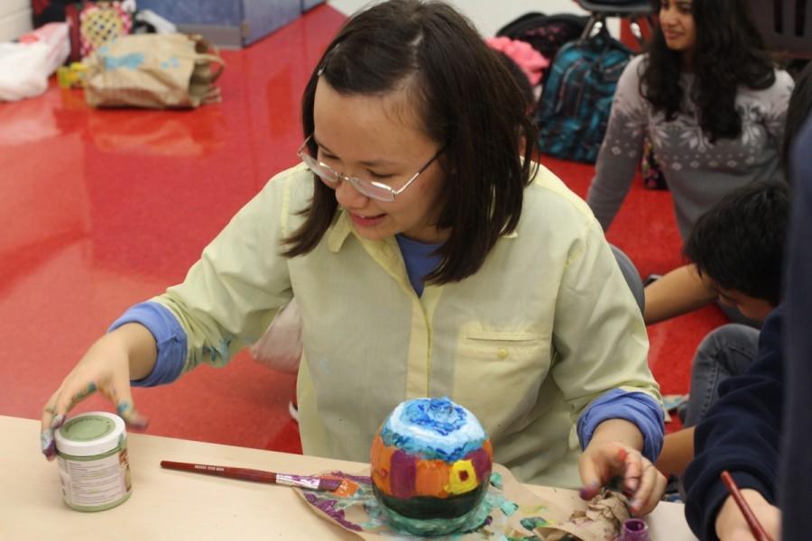 Junior Victoria Bevard grabs more paint to work on her pumpkin