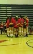 The Varsity Volleyball team huddles before the game begins.