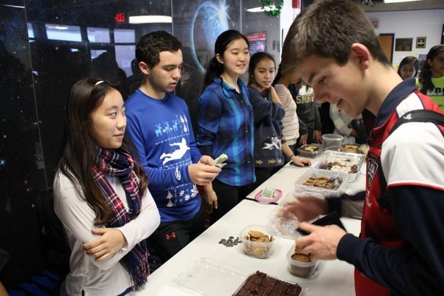 Sophomore Alex Lewis eyes the baked goods at the LIFE bake sale. The bake sale was held on Dec. 16 in the JLounge in order to raise funds.