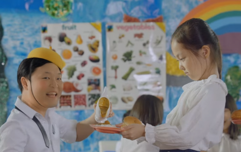South Korean artist Psy portrays a boy pouring curry onto rice for an adoring girl in his music video for