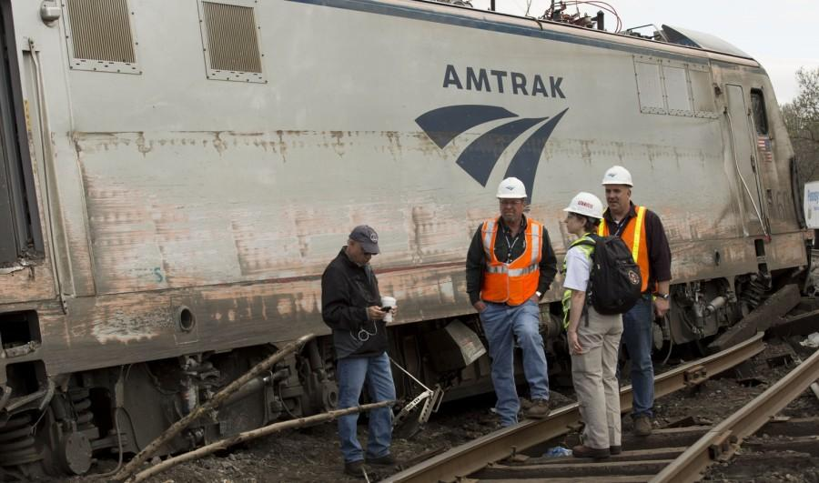 Investigators inspect the derailed train. It was later determined that the train was traveling two times faster than the recommended speed for the area of track it was on.