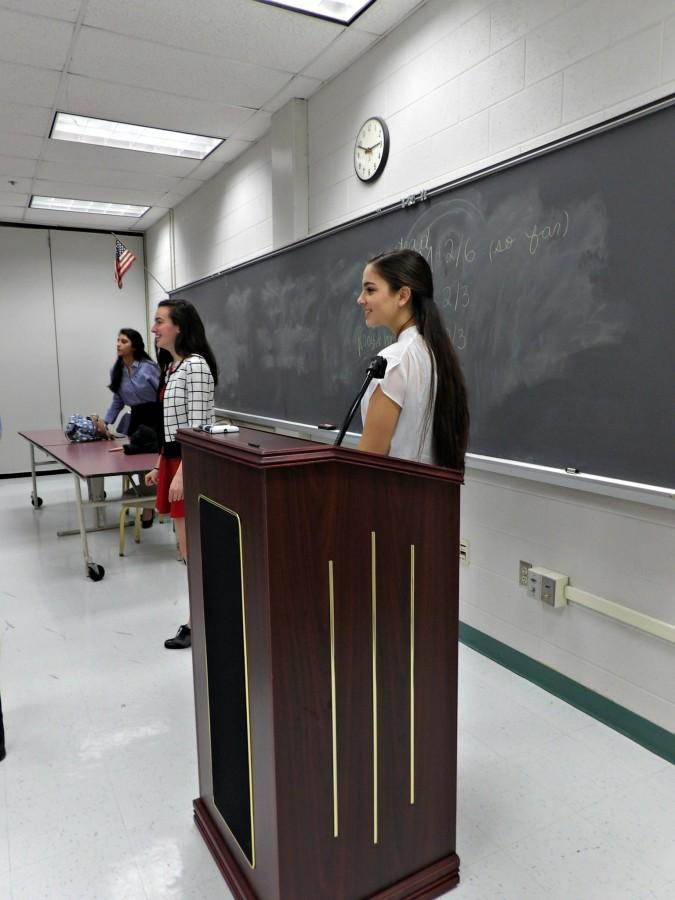 Sophomore Artemis Veizi and sophomore Mara Casebeer talks to the delegates at the podium for the last session of Chantilly Model United Nations Conference.