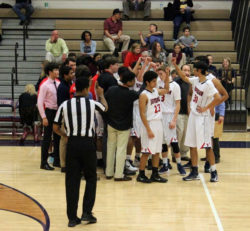 During a time-out, the varsity team ends their strategic huddle with a cheer.