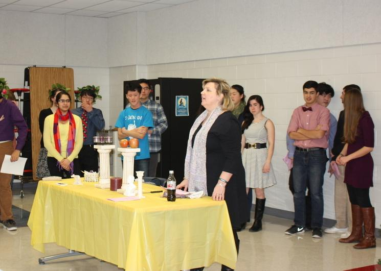 Latin teacher Christine Conklin leads students through the Latin Honor Society Induction Ceremony.  The ceremony took place on Jan. 20 in the cafeteria, and allowed students to journey through their years of the language before Latin Honor Society officers completed the induction.