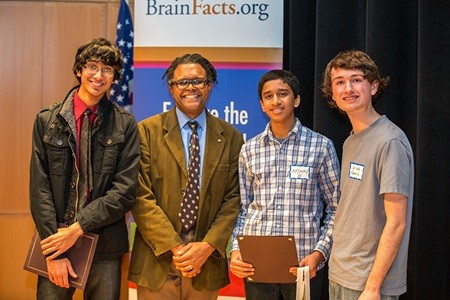 Winner Shomik Ghose (far left), Runner-up Akshay Balaji (center right), and 3rd place Winner Jacob Gerrish (far right) stand alongside DC Brain Bee Moderator Benjamin Walker (center left) in victory after the competition concludes.
