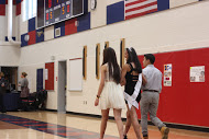 Senior Cece Xiao walks across the gym with escorts, senior Helen Ngov and junior Chris Cao as she is recognized as a senior dance team member.