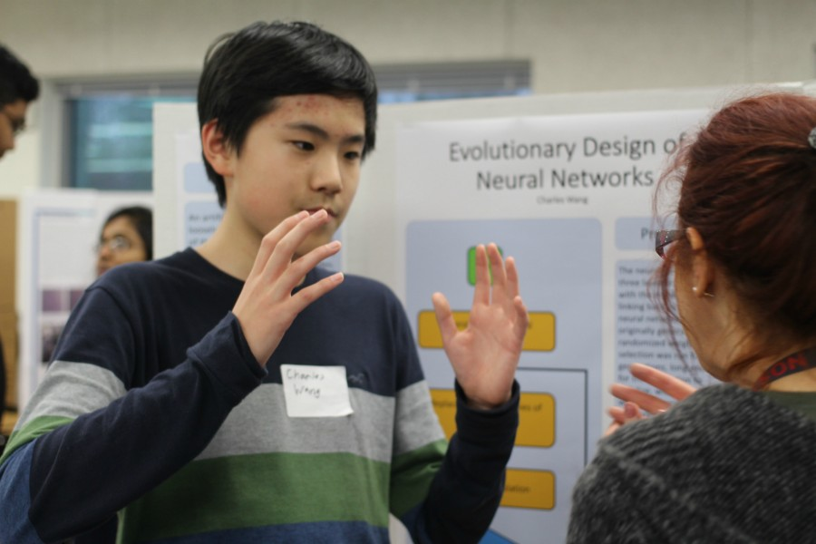 Sophomore Charles Wang explains his science fair project to biology teacher, Dr. Del Cerro.
