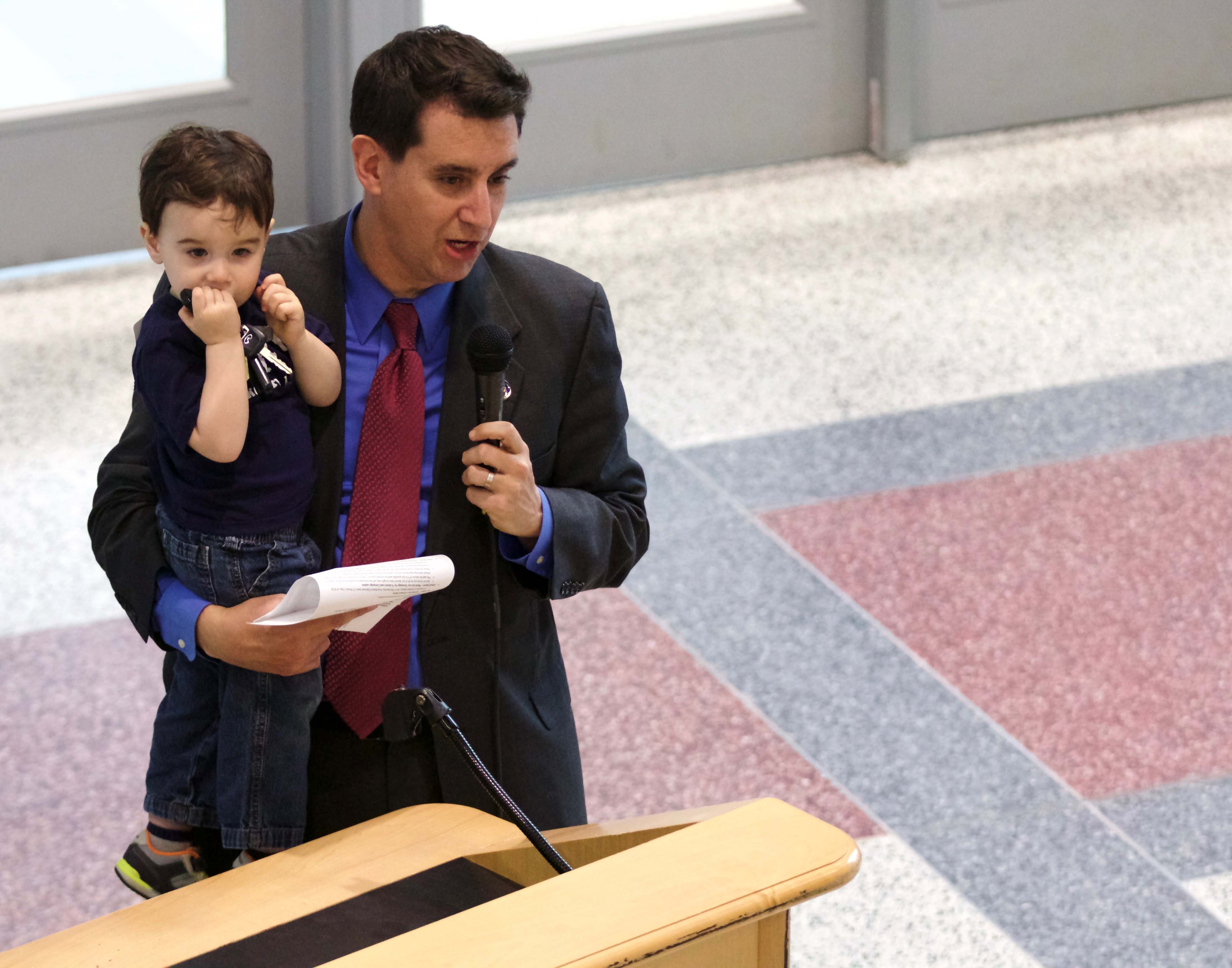 Holding his son Luke, Dr. Evan Glazer gives opening remarks at the dome opening ceremony on March 10. Glazer has served as principal of TJHSST for the last ten years.