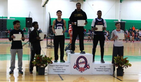 Senior Charlie Guan stands on the podium to receive his award. He placed second overall in the 55m hurdles, breaking his own Jefferson school record.