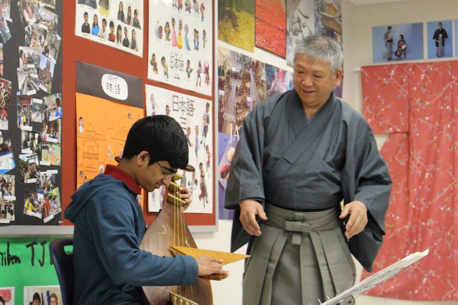 Student tries out the biwa as the satsuma-biwa master watches how well he is doing.