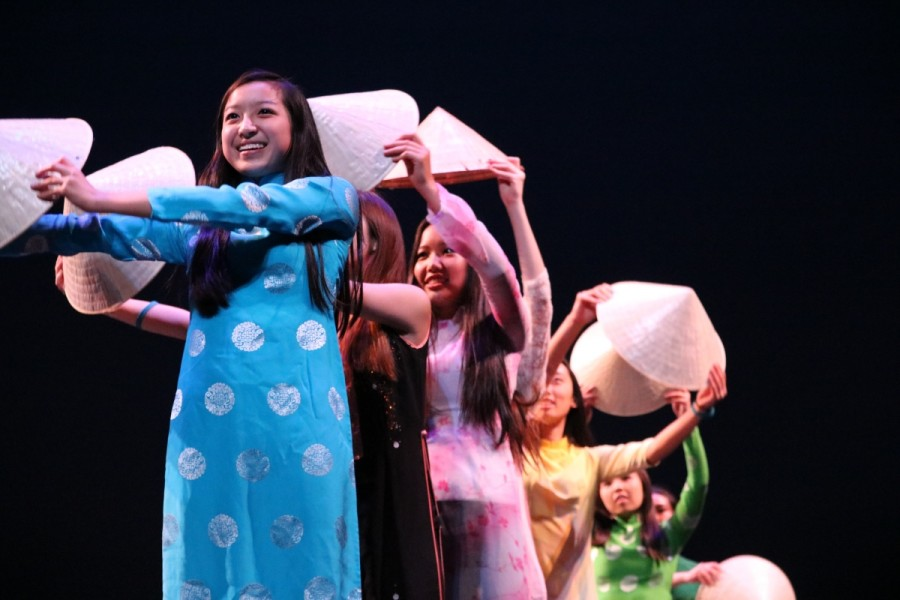 Sophomore Melanie Le and the other performers create a wave with traditional hats for the Japanese Culture Clubs performance.
