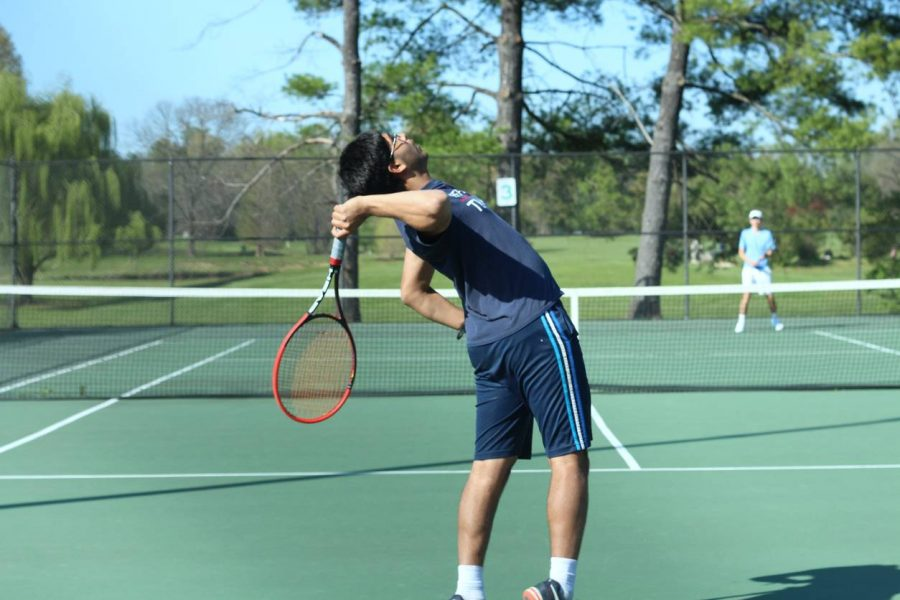 Reaching back, junior Neeraj Prasad serves the ball to his opponent in his singles match.