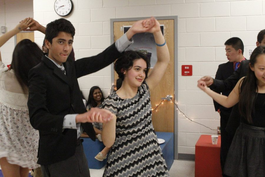 Sophomore Neel Shah watches the dance instructor as he attempts to spin sophomore Maya Parker as taught.