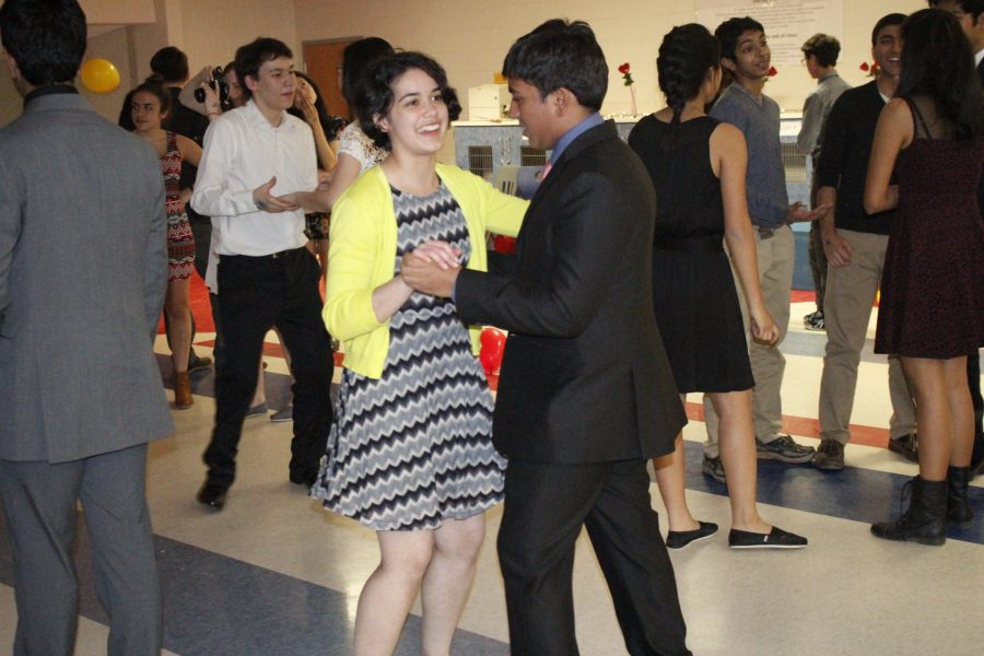 Sophomores Maya Parker and Paarth Jain dance together on the dance floor, surrounded by other dancing pairs.