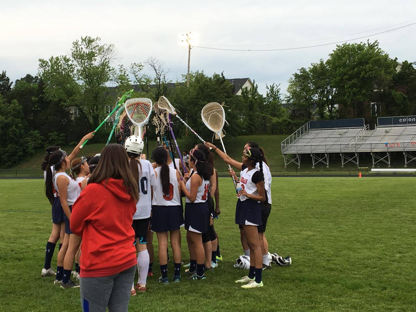 Junior Varsity lacrosse  players salute their final game's victory through a ceremonial bashing of lacrosse sticks.