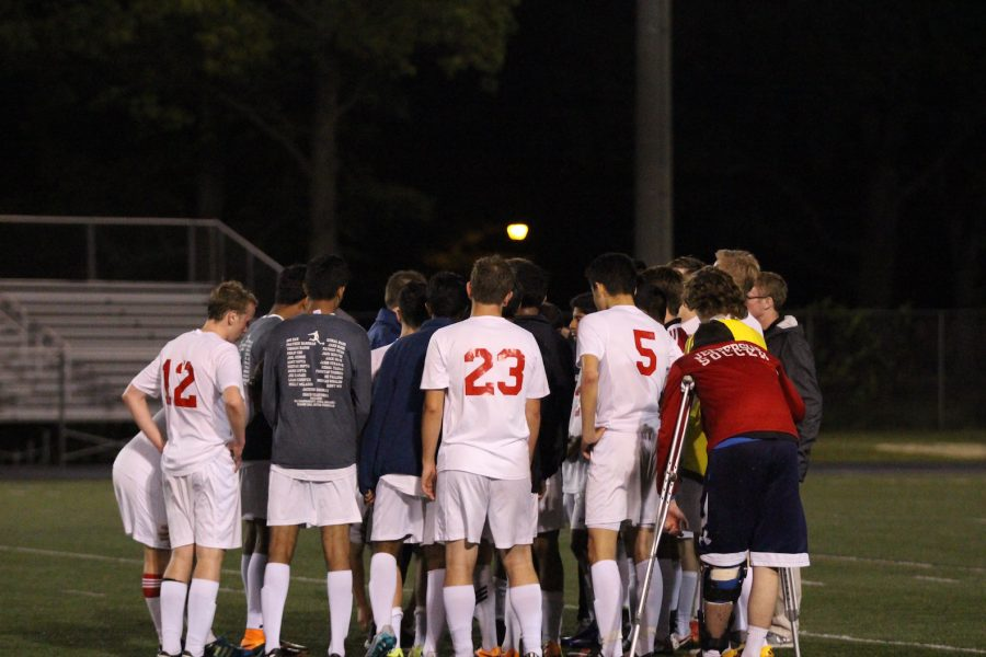 The+athletes+huddle+after+their+win+of+2-0.