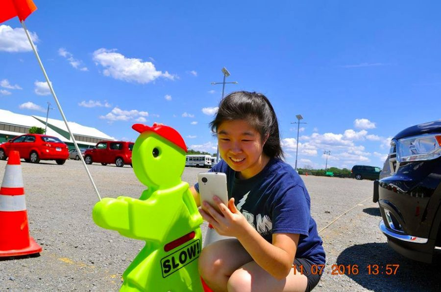 Rising junior Lilian Wang crouches in a parking lot as she spots another Pokémon