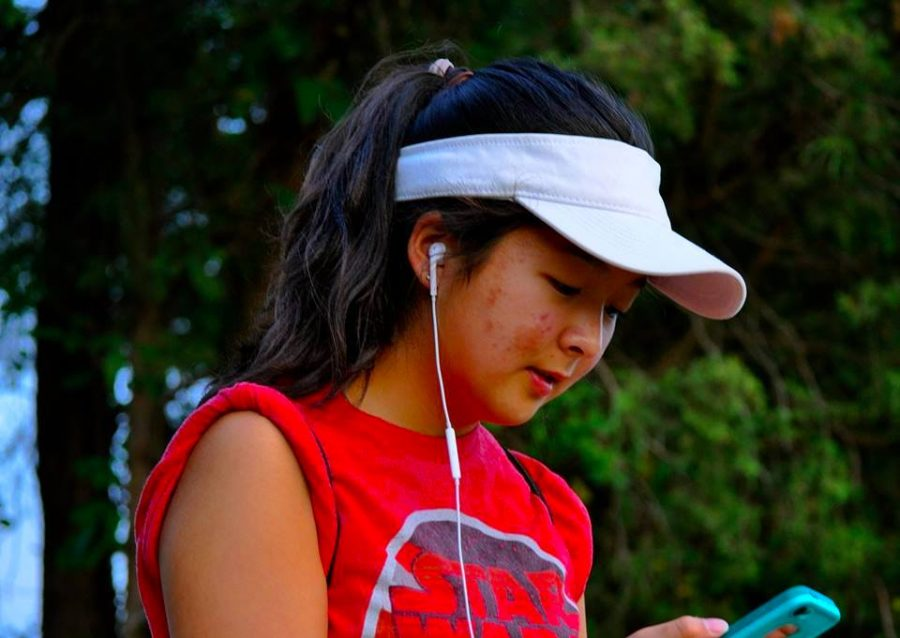 Rising junior Sophie Koh stares as her phone as she finds a Pokémon