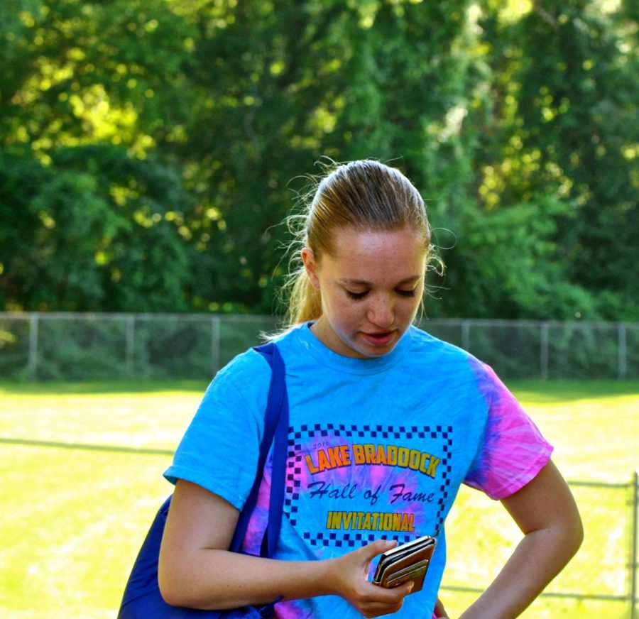 Rising senior Caroline Cox stares intently at her phone while playing 'Pokémon Go'