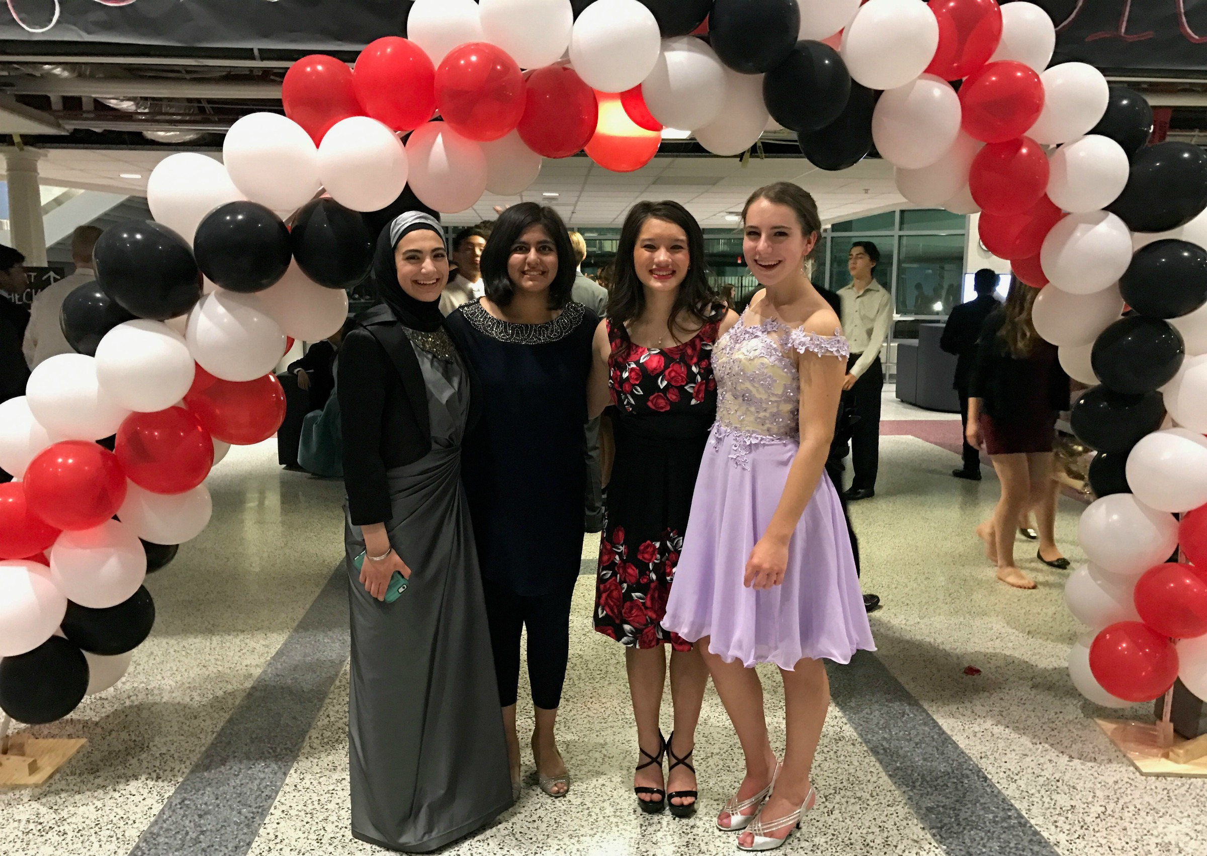 At the dance, students pose in front of the balloon arch for homecoming pictures.