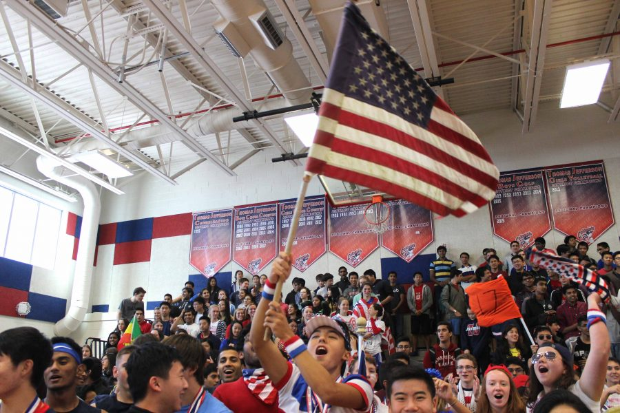 Senior Nick Yoon raises an American flag above members of the Class of 2017 to start off the pep rally during lunch on Tues., Oct. 11.