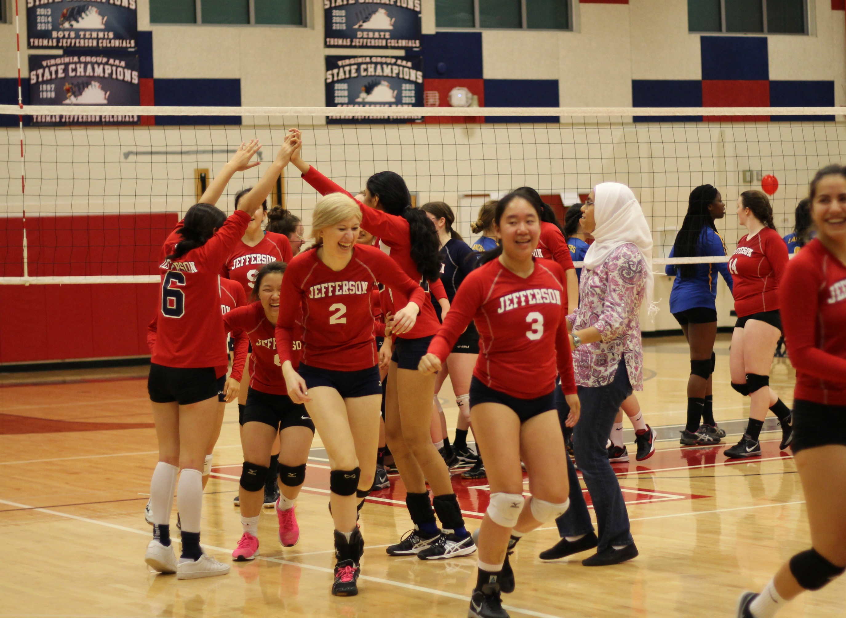 The+varsity+volleyball+team+smile+as+the+run+by+JV+volleyball+members+cheering+them+on+after+their+win.