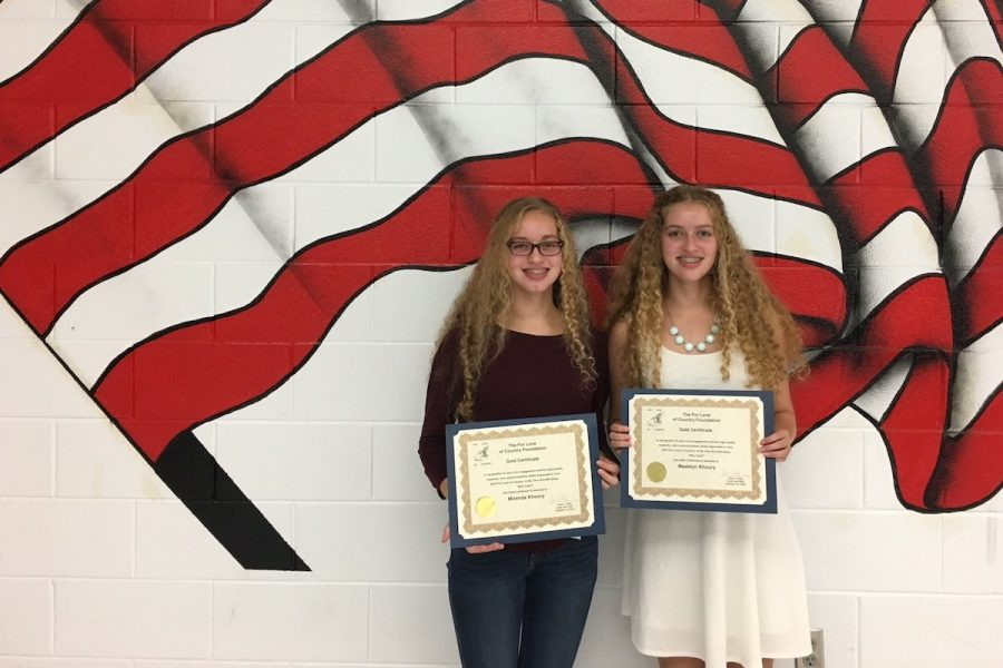 Madelyn+and+Miranda+Khoury+hold+up+their+certificates+honoring+their+%22For+Love+of+Country%22+essays.