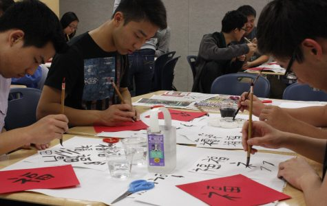 Students practice writing Chinese characters on red paper using Chinese calligraphy brushes in a Chinese Honor Society cultural event. The event took place on Nov. 18 during eighth period.